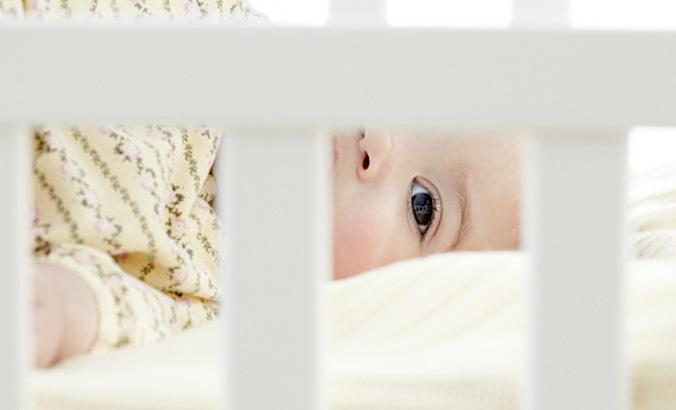 Baby schaut durch Gitterbett